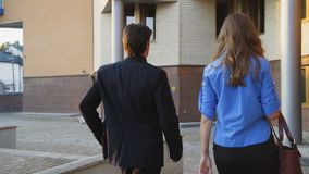 Back view of two business partners discussing issue on the way to office 4K.  stock footage
