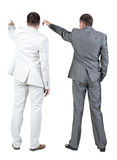 Back view of two businessman pointing at wall. rear view. Royalty Free Stock Photography