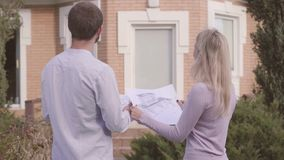 Back view of two Caucasian people standing in front of the house with architectural drawings and talking. Professional stock footage