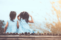 Back view of two child girls sitting and looking at nature Stock Image