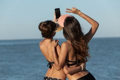 Back view of two dark-haired girls in swimsuits and caps in embrace make a selfie near the sea on a sunny day. stock photography