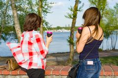 Back view two female friends. Drinking coffee and watching the water. Background nature, park, river Royalty Free Stock Image