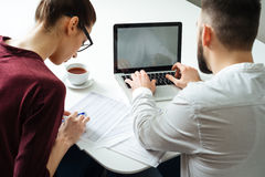 Back view of two focused serious businesspeople using laptop stock photos