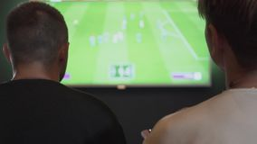 Back view of two guys playing video game in the gaming room sitting on the sofa. Friends playing football or soccer. Back view of two guys playing the video game stock video footage