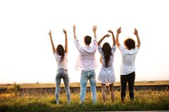 Back view. Two guys and two girls are standing in the field on a summer day and holding their hands up.  stock photography