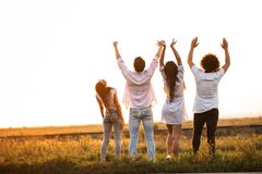 Back view. Two guys and two girls are standing in the field on a summer day and holding their hands up.  stock images
