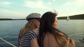 Back view of two lesbians hugging and enjoying voyage on sailboat. Young people on vacation. lgbt, gay couple, summer holidays stock video