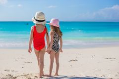 Back view of two little girls looking at the sea on white beach Royalty Free Stock Photo