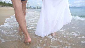 Back view of two lovers walking on the seaside and hugging. Legs on sand.  stock footage