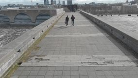 Back view of two man with guitars walking on a large grey bridge against blue cloudy sky and city buildings in early. Spring. Urban architecture stock footage
