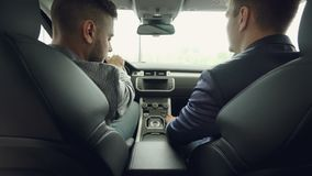 Back view of two men car dealer and customer talking discussing automobile model while sitting on front seats in. Back view of two handsome men car dealer and stock video footage