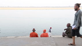Back view of two men sitting on the ghats of the Ganges river in Varanasi. stock video footage