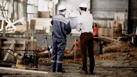 Back view of two men standing together in construction area and looking at shop drawings of future structure. Foreman in. Back view of two men in white safety stock video