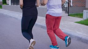 Back view of two people in motion of jogging on street stock video footage