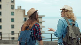 Back view of two pretty girls young women friends travelers walking outdoors.  stock footage