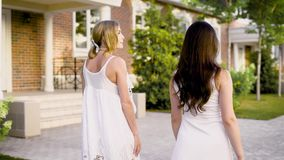 Back view of two stylish girls walking along street and chatting in summertime. Two young women in white dresses walking at street and talking stock video footage