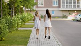 Back view of two stylish women in white walking on pavement and talking. Anonymous girls in dresses walking along street and having talk stock video