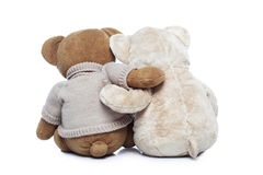 Back view of two Teddy bears hugging each other. Over white background Royalty Free Stock Photo