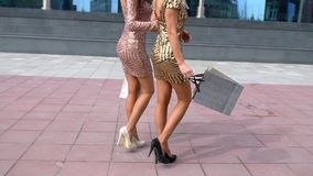 Back view of two walking women with shopping bags. slow-motion. close-up of female legs in high heels. close-up of. Female legs in high heels. with shopping stock video