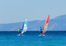 Back view of two windsurfers in action mooving parallel to each other Royalty Free Stock Images