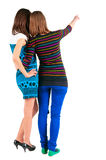 Back view of two young  brunette woman pointing at wall Royalty Free Stock Images