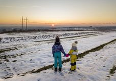 Back view of two young children in warm clothing standing in frozen snow field holding hands on copy space background of setting. Sun and clear blue sky stock photo
