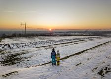 Back view of two young children in warm clothing standing in frozen snow field holding hands on copy space background of setting. Sun and clear blue sky royalty free stock photography