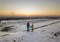 Back view of two young children in warm clothing standing in frozen snow field holding hands on copy space background of setting. Sun and clear blue sky royalty free stock images