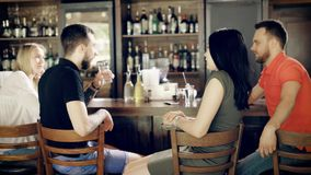 Back view of two young couples sitting at bar counter drinking beverages while the barman is working with window case. Back view of two young couples relaxing in stock footage