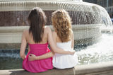 Back view of two young female friends with arms around sitting by water fountain Royalty Free Stock Images