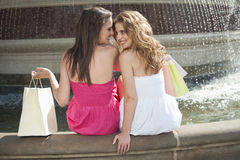 Back view of two young female friends communicating while sitting by water fountain Royalty Free Stock Photo