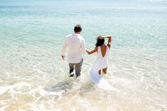 Back view of a two young just married couple enter in clothing in water, summer time, holiday in Greece. Honeymoon. royalty free stock images