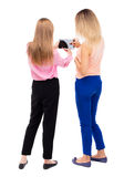 Back view of two young woman look at the smart phone. Royalty Free Stock Images
