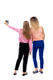 Back view of two young woman photographed on a mobile phone. Royalty Free Stock Photo