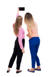 Back view of two young woman photographed on a mobile phone. Stock Image