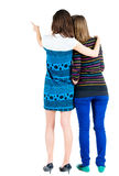 Back view of two young woman  pointing at wall . Stock Photos