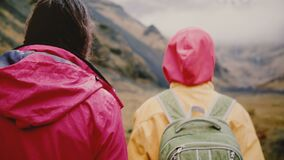 Back view of two young women with backpacks walking in mountains. Tourists hiking together early in the foggy morning.