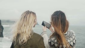 Back view of two young women taking selfie photos on the shore of the sea near the troll toes rocks in Iceland. Traveling female enjoying the beautiful stock video