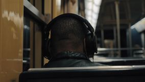 Subway commuter enjoying music during the ride. Back view of unidentified black man listening to favourite music in headphones when traveling by subway stock video footage