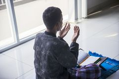 Unknown man prays to the Allah at home. Back view of unknown man praying to the Allah after reading Quran near the window at home royalty free stock images