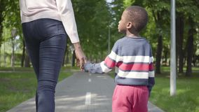 Back view of unrecognizable African American woman walking in the park with her little son, holding hands. Cute child. Back view of unrecognizable African stock video footage
