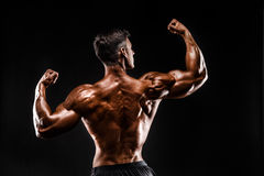 Back view of Unrecognizable man, strong muscles posing with arms up Royalty Free Stock Photos