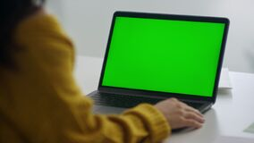 Free Back View Unrecognized Woman Looking Green Screen Laptop Computer In Office. Stock Images - 186334654