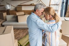 back view of upset senior couple embracing while standing between cardboard boxes royalty free stock image