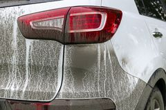 Back view of a very dirty car. Fragment of a dirty SUV. Dirty headlights, wheel and bumper of the off-road car with swamp splashes royalty free stock photography