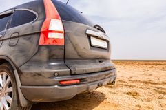 Back view of a very dirty car. Fragment of a dirty SUV. Dirty rear lights, wheel and bumper of the off-road car with sand dust on. A side panel Royalty Free Stock Photo