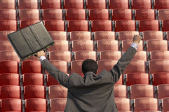 Back view of victorious businessman with briefcase facing rows of red seats at stadium Royalty Free Stock Photos