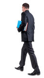 Back view of walking  business man with books. Stock Photos