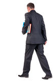 Back view of walking  business man with books Royalty Free Stock Images