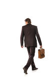 Back view of walking business man. Back view of a walking business man holding a briefcase and looking to his side on white background Royalty Free Stock Photography